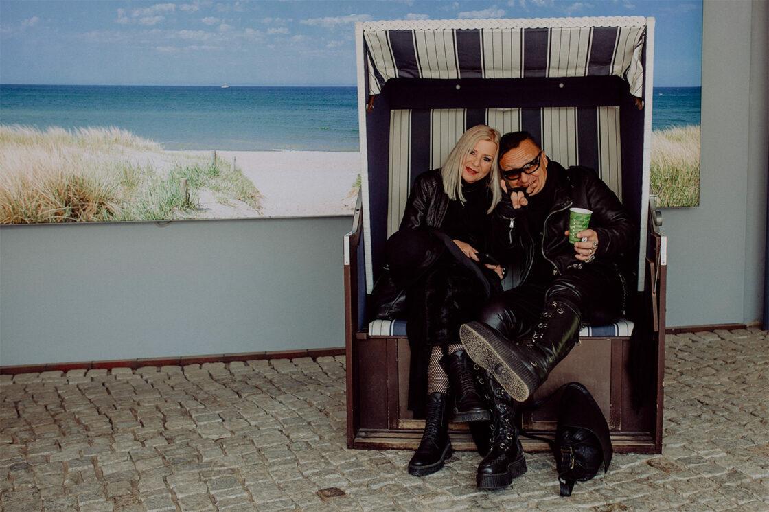 Schwarz gekleidetes Paar in Strandkorb, die das Plage Noire Festival besuchen.